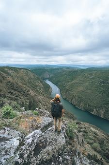 Pionowe ujęcie męskiego turysty w sil canyon w hiszpanii