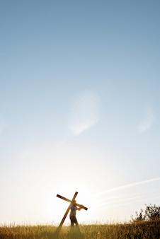 Pionowe ujęcie mężczyzny niosącego duży drewniany krzyż w trawiastym polu z błękitnym niebem