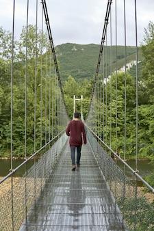 Pionowe ujęcie mężczyzny przechodzącego przez most wiszący las caldas w asturii, hiszpania