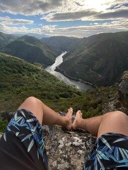 Pionowe ujęcie mężczyzny siedzącego na kamieniu w kanionie sil w hiszpanii