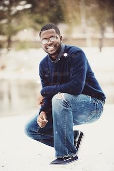 Pionowe ujęcie mężczyzny uśmiecha się do kamery w pozycji kucanej w śnieżny dzień