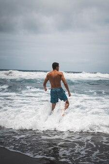 Pionowe ujęcie mężczyzny w stroju kąpielowym stojącego nad morzem
