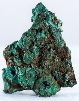 Pionowe ujęcie minerału malachitu na białym tle