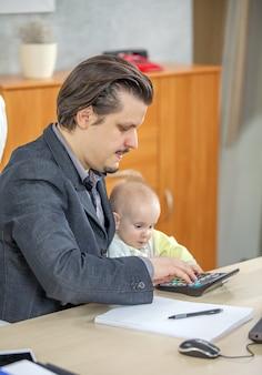 Pionowe ujęcie młodego biznesmena pracującego w swoim biurze i posiadającego dziecko