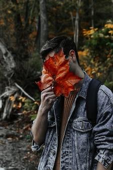 Pionowe ujęcie młodego mężczyzny zakrywającego całą twarz dużym złotym jesiennym liściem