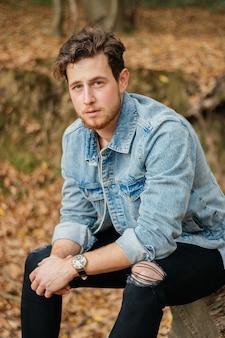 Pionowe ujęcie młodego przystojnego faceta w jesiennym parku