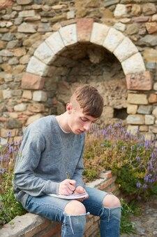 Pionowe ujęcie młodego stylowego kaukaskiego faceta siedzącego w ogrodzie odrabiającego pracę domową