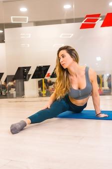 Pionowe ujęcie młodej kaukaskiej kobiety robiącej rozciąganie na siłowni