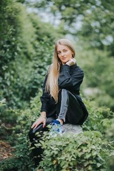 Pionowe ujęcie modnej kaukaskiej blondynki pozującej w otoczeniu zieleni
