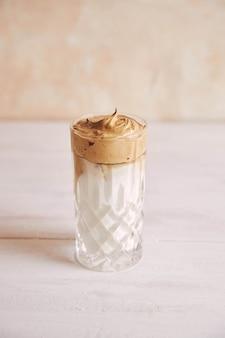 Pionowe ujęcie modnej pysznej świeżej kawy dalgona z mlekiem na białym drewnianym stole