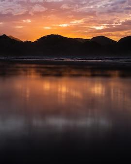 Pionowe ujęcie morza z górami w oddali o zachodzie słońca