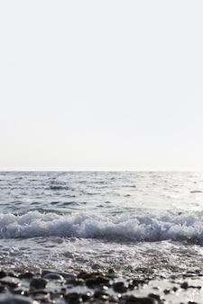 Pionowe ujęcie morza z pięknymi falami i czystym białym niebem