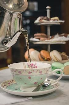Pionowe ujęcie nalewania herbaty w filiżance na marmurowym stole z deserami