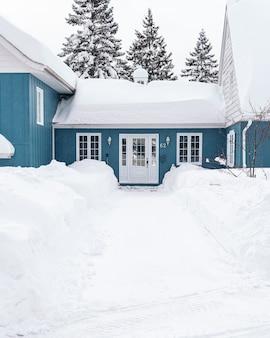 Pionowe ujęcie niebieskiego domu pokrytego białym śniegiem zimą