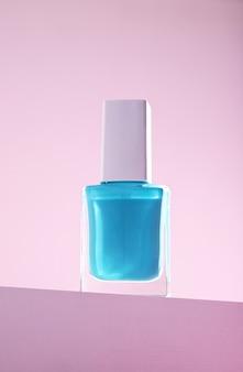 Pionowe ujęcie niebieskiego lakieru do paznokci na różowej ścianie