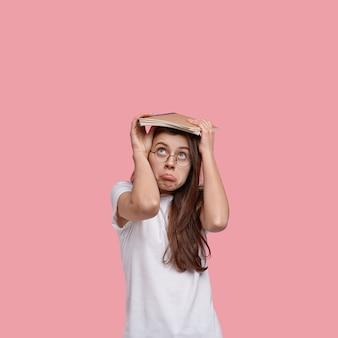 Pionowe ujęcie nieszczęśliwej kobiety torebki usta, obejmuje głowę notatnikiem, ubrana w biały t shirt