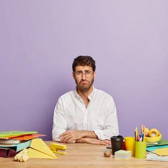 Pionowe ujęcie niezadowolonego mężczyzny z ponurym wyrazem twarzy, pracuje w biurze, smutny z powodu codziennych problemów, zmęczony długimi godzinami pracy, nosi okulary i białą koszulę