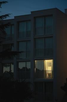 Pionowe ujęcie nowoczesnego białego budynku ze światłem wydostającym się z jednego z dużych okien balkonowych