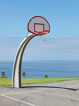 Pionowe ujęcie obręczy do koszykówki w pobliżu morza pod pięknym błękitnym niebem