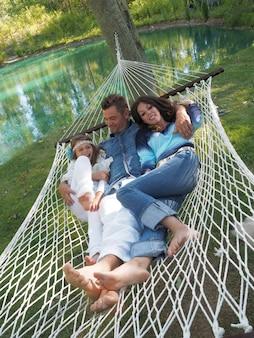 Pionowe ujęcie ojca, matki i córki leżących na hamaku w ogrodzie