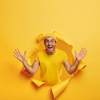 Pionowe ujęcie optymistycznego człowieka stwarzających przez rozdarty papier