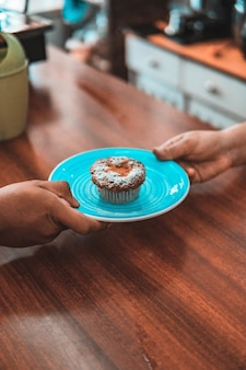 Pionowe ujęcie osób trzymających talerz smacznego ciastka w kawiarni