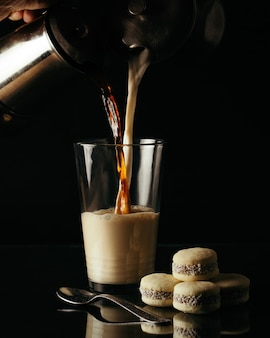 Pionowe ujęcie osoby nalewania herbaty i mleka w szklance na stole z ciasteczkami