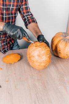 Pionowe ujęcie osoby w rękawiczkach podczas cięcia dyni na halloween