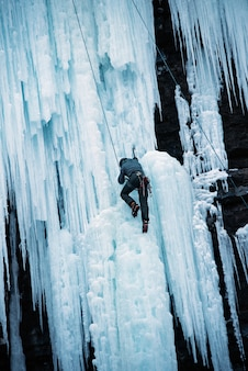 Pionowe ujęcie osoby wspinającej się po skalistym klifie pokrytym lodem