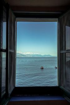 Pionowe ujęcie otwartego okna z widokiem na piękne morze