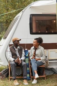 Pionowe ujęcie pełnometrażowe młodej pary z afryki, relaksującej się na świeżym powietrzu podczas biwakowania ze szlakiem...
