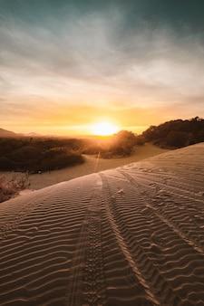 Pionowe ujęcie piaszczystych wzgórz na pustyni z zapierającym dech w piersiach zachodem słońca