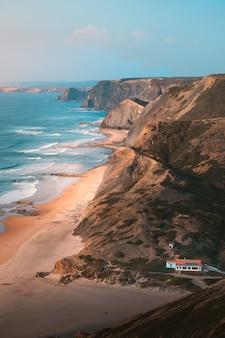 Pionowe ujęcie pięknego oceanu przez skalistą skałę i góry pod jasnym błękitnym niebem