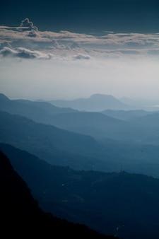 Pionowe ujęcie pięknego pasma górskiego i pochmurnego nieba wczesnym rankiem