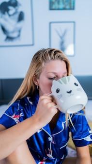 Pionowe ujęcie pięknej młodej damy w piżamie pijącej poranną kawę