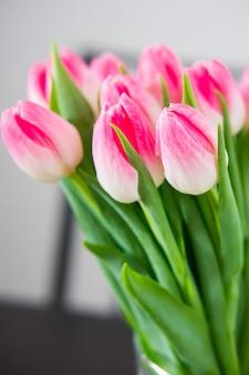 Pionowe ujęcie pięknych różowych tulipanów z zielonymi liśćmi