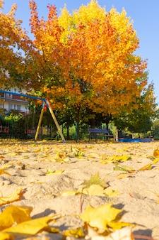 Pionowe ujęcie placu zabaw w parku z kolorowymi liśćmi w ziemi jesienią