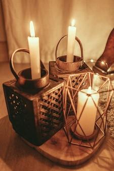Pionowe ujęcie płonących świec z pięknym wystrojem świeczników
