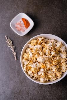Pionowe ujęcie płyty popcornu pod dużym kątem w pobliżu małego talerza z przyprawami na szarej powierzchni