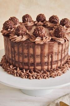 Pionowe ujęcie pod wysokim kątem świeżego ciasta czekoladowego ozdobionego pyszną czekoladą na talerzu