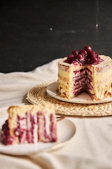 Pionowe ujęcie pokrojonego ciasta wiśniowego w oddali