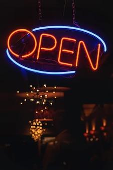 """Pionowe ujęcie pomarańczowo-niebieskiego neonu z napisem """"otwórz"""" przy barze"""