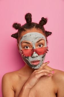 Pionowe ujęcie poważnej, spokojnej kobiety stojącej nagim ciałem, trzymającej dłoń pod brodą, nakładającej glinianą maskę, dba o skórę, nosi stylowe okulary przeciwsłoneczne, pięknie wygląda. pielęgnacja twarzy i zabiegi spa
