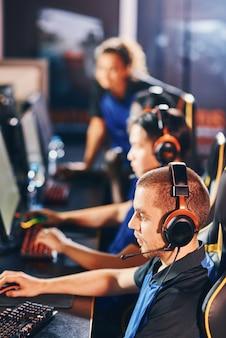 Pionowe ujęcie profesjonalnych graczy cybersportowych w słuchawkach siedzących w rzędzie, grających w gry wideo online podczas udziału w turnieju esportowym, skupiających się na kaukaskim facecie