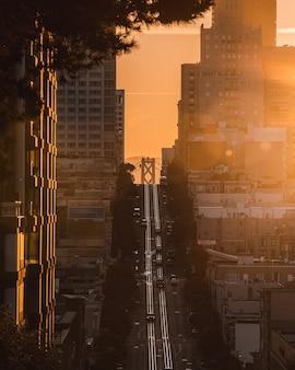 Pionowe ujęcie przedstawiające drogę pod górę pośrodku budynków z prowadzącymi samochodami