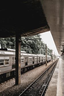 Pionowe ujęcie przystanku z szarym metalicznym pociągiem odjeżdżającym