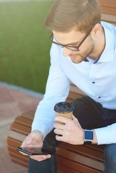 Pionowe ujęcie przystojnego biznesmena używającego smartfona i pijącego kawę podczas relaksu na