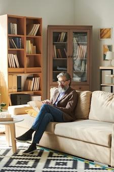 Pionowe ujęcie przystojnego brodatego mężczyzny w stylowym stroju siedzącego zrelaksowanego na kanapie w nowoczesnym pokoju biurowym robienia notatek