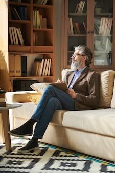 Pionowe ujęcie przystojnego brodatego mężczyzny w stylowym stroju z okularami, siedzącego na kanapie w nowoczesnym pokoju biurowym, trzymając schowek, odwracając wzrok