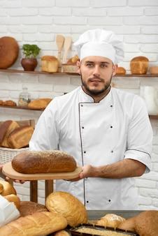 Pionowe ujęcie przystojnego młodego piekarza oferującego bochenek ciemnego, smacznego i aromatycznego chleba